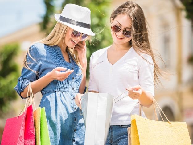 Twee mooie vrouwen die binnen het winkelen zakken in stad kijken. Premium Foto