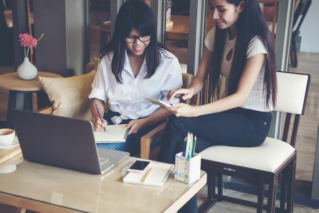 Twee mooie vrouwen die in een koffiewinkel werken Gratis Foto