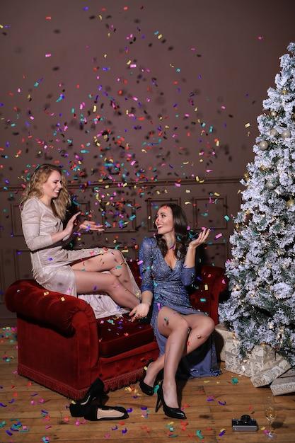 Twee mooie vrouwen die kerstmis samen met manierkleding vieren. kerst thuis Gratis Foto