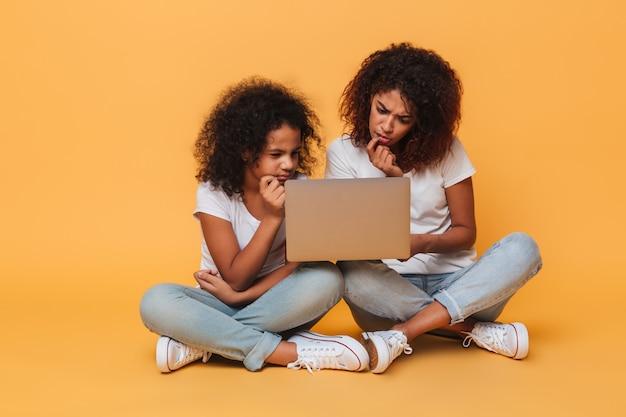 Twee nadenkende afro-amerikaanse zusters die laptop computer met behulp van Gratis Foto