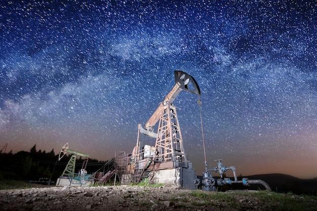 Twee oliepompen werken in het olieveld in de nacht onder melkweg. olie-industrie apparatuur Premium Foto