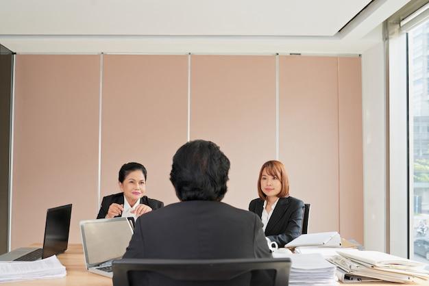 Twee ondergeschikte werknemers die rapporteren aan de topmanager van een bedrijf Gratis Foto