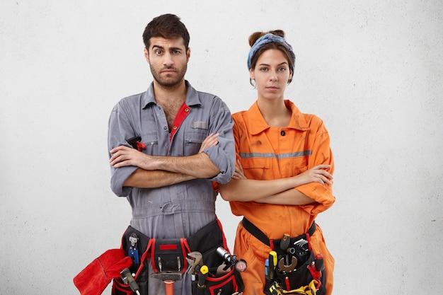 Twee onderhoudsmedewerkers staan naast elkaar, houden de handen gevouwen, trekken verbijsterd wenkbrauwen op, Gratis Foto