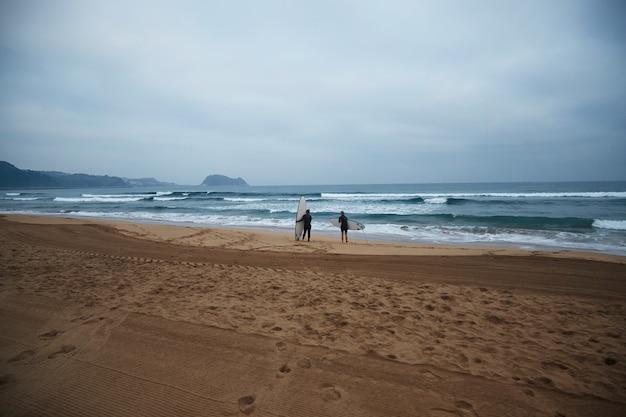 Twee onherkenbare surfmeisjes met hun longboards blijven aan de oever van de oceaan en kijken 's ochtends vroeg naar golven, in volledige wetsuits en klaar om te surfen Gratis Foto