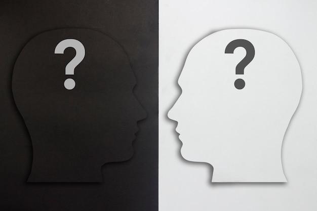 Twee papierkoppen met een vraagteken, zwart en wit op een zwart-witte achtergrond. het concept van een gespleten persoonlijkheid, verschillende meningen, geschillen, oorlog. plat lag, bovenaanzicht. Premium Foto