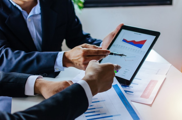 Twee partner bedrijfsmenseninvesteerder die over de informatie van de financiële statistiekengrafiek spreken Premium Foto