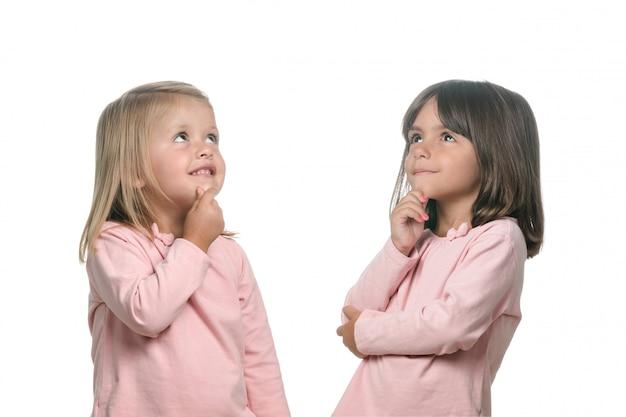 Twee peinzende kleine meisjes die aan iets denken Premium Foto