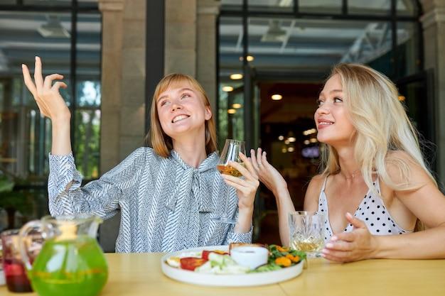 Twee positieve blanke vrouwen brengen graag tijd samen door in een restaurant Premium Foto