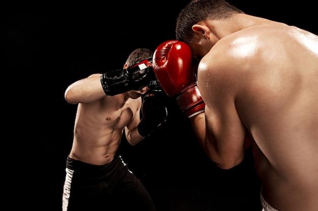 Twee professionele bokser boksen op zwarte muur Gratis Foto