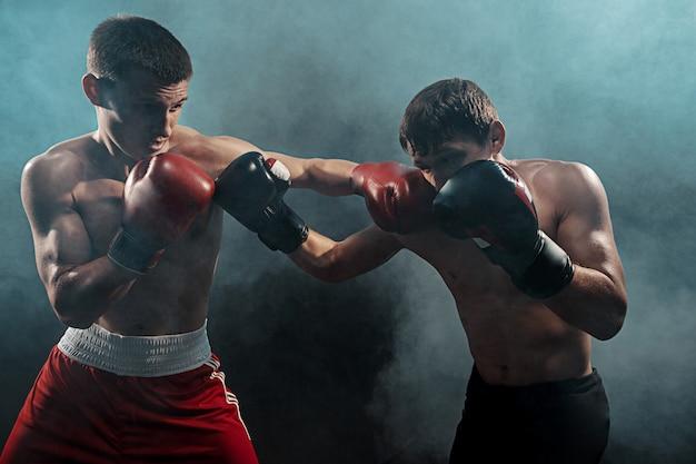 Twee professionele bokser boksen op zwarte rokerige, Gratis Foto