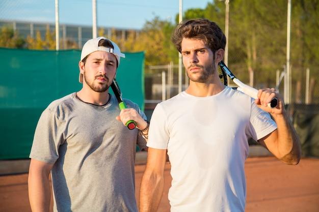 Twee professionele tennisspelers met jongens met een hard gezicht op een tennisbaan. Premium Foto