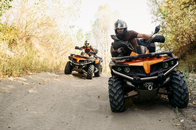 Twee quadrijders in helmen reizen in bos, vooraanzicht. rijden op atv, extreme sporten en reizen, quadbike-avontuur Premium Foto
