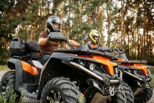 Twee quadrijders in helmenclose-up, zijaanzicht Premium Foto
