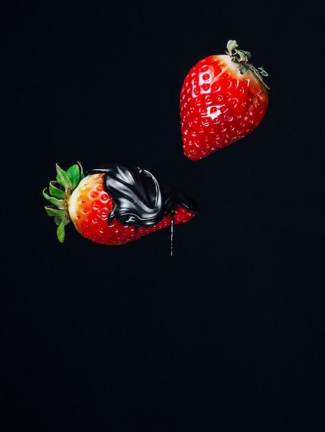 Twee rode verse sappige aardbeien in chocolade op het zwarte vallen vallen als achtergrond Premium Foto