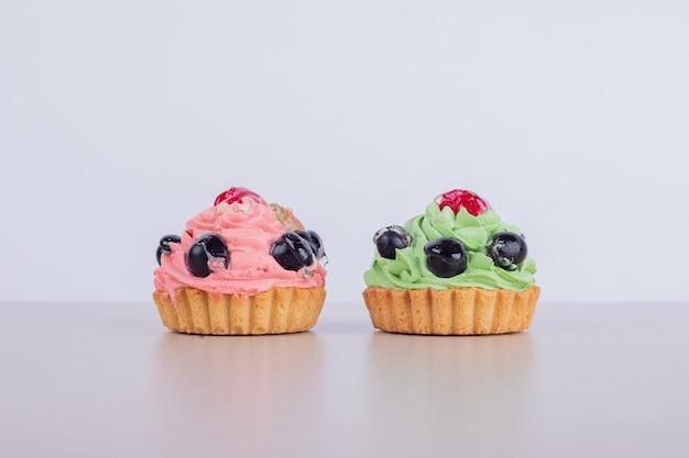 Twee romige cupcakes op wit. Gratis Foto