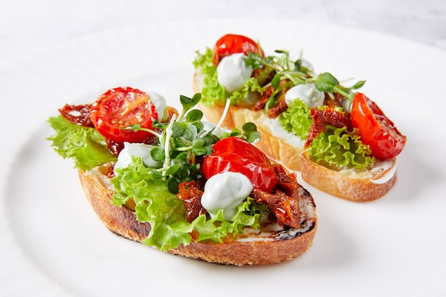 Twee sandwiches met groenten op wit bord, met tomaat, sla, kruiden, mayonaise en saus Premium Foto