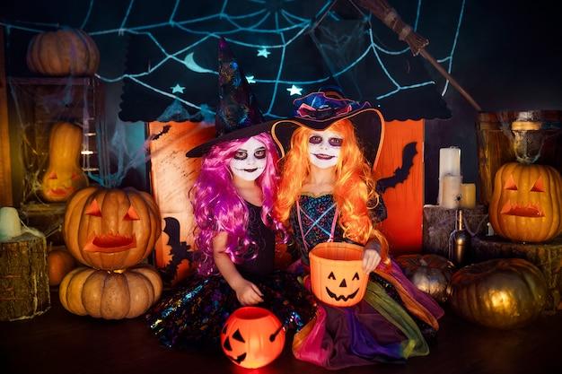 Twee schattige grappige zussen vieren de vakantie. heel kinderen in carnaval-kostuums klaar voor halloween. Premium Foto