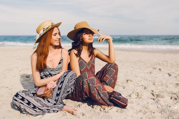 Twee schattige jonge vrouwen die op het strand zitten Gratis Foto