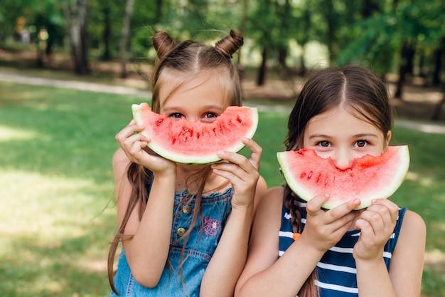 Twee schattige kleine meisjes die watermeloen in park in zomer eten Premium Foto