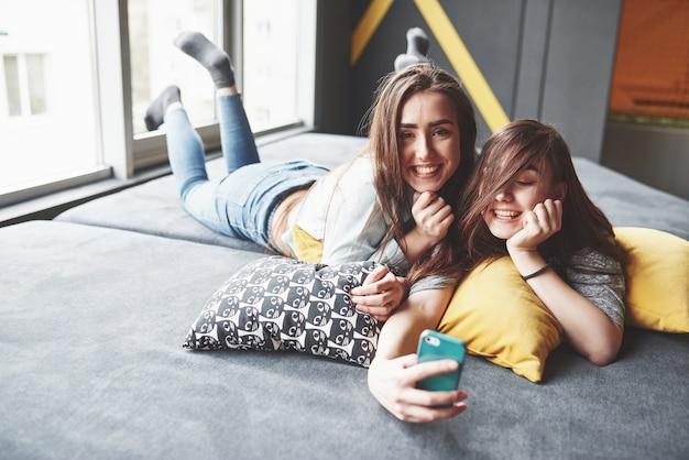 Twee schattige lachende tweelingzusjes smartphone houden en selfie maken. Gratis Foto
