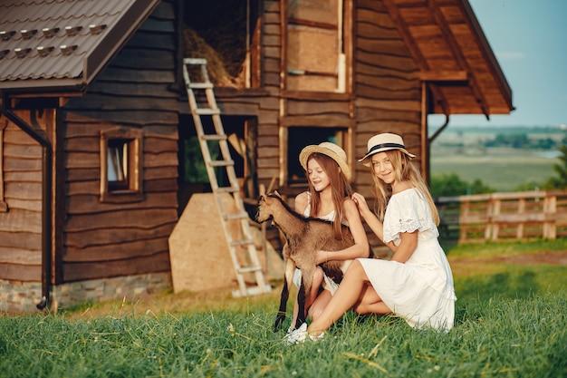 Twee schattige meisjes in een veld met een geit Gratis Foto