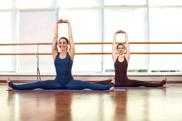 Twee schattige slanke jonge vrouwen doen de yoga pose terwijl ze in een lichte sportschool in de buurt van een groot raam staan. Premium Foto