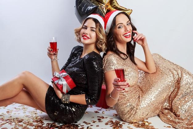 Twee sexy vrouwen in in rode kerst kerstman vakantie hoed zittend op de vloer met glanzende gouden confetti Gratis Foto