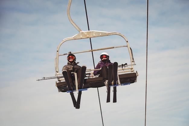 Twee skiërs die in skilift bij skitoevlucht reizen Gratis Foto