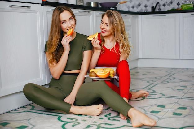 Twee sportmeisjes in een keuken met groenten Gratis Foto