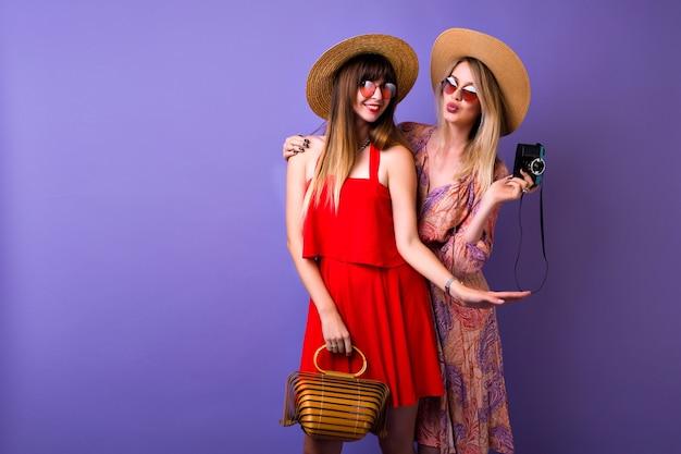 Twee stijlvolle hipster meisjes samen plezier, vintage boho jurk hoeden en accessoires, blonde vrouw foto's maken van haar beste vriend, Gratis Foto