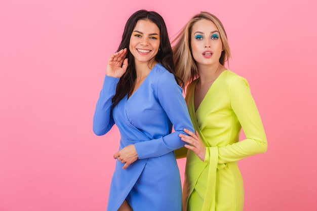 Twee stijlvolle lachende aantrekkelijke vrouwen vrienden poseren op roze muur in stijlvolle kleurrijke jurken van blauwe en gele kleur, lente modetrend Gratis Foto