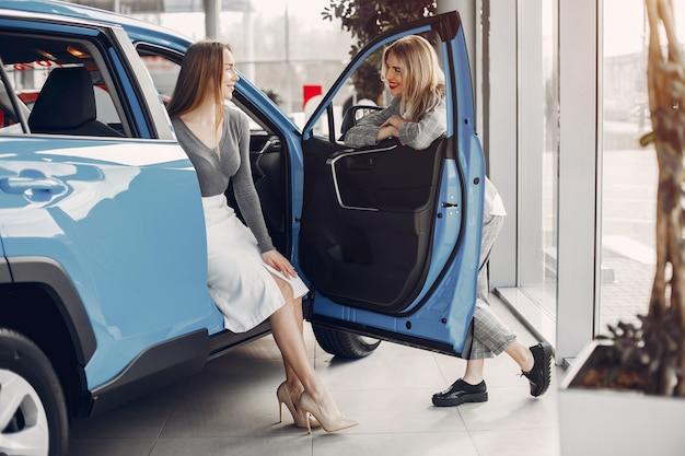 Twee stijlvolle vrouwen in een autosalon Gratis Foto