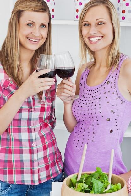 Twee stralende vrouwen die wijn na het koken in de keuken drinken Premium Foto