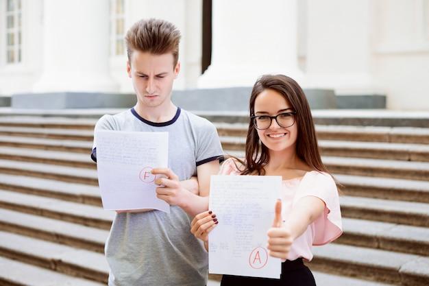 Twee studenten met testresultaten. gelukkige vrouwelijke student heeft een uitstekend a-cijfer behaald, maar haar mannelijke vriend heeft de test niet gehaald en heeft een laag cijfer gekregen voor zijn werk Premium Foto