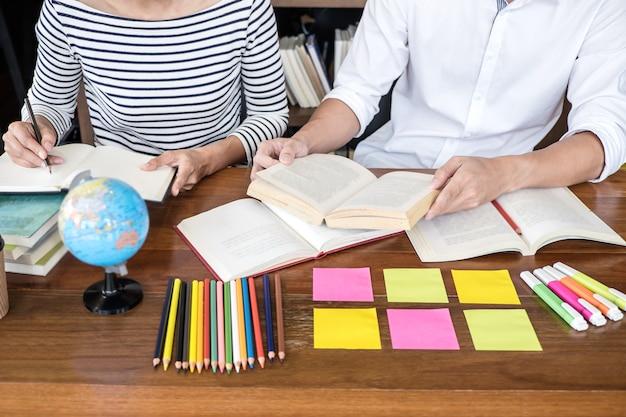 Twee studentengroep van de middelbare schoolzitting in bibliotheek met hulpvriend die thuiswerk en lessenpraktijk doet Premium Foto
