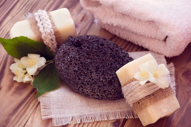 Twee stukken droge zeep met een jasmijn, handdoek en puimsteen Premium Foto