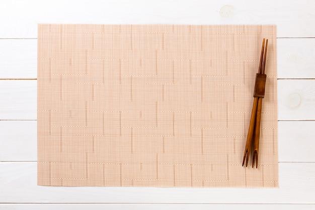 Twee sushieetstokjes met lege bruine bamboemat of houten plaat op witte houten hoogste mening met copyspace. lege aziatische voedselachtergrond Premium Foto