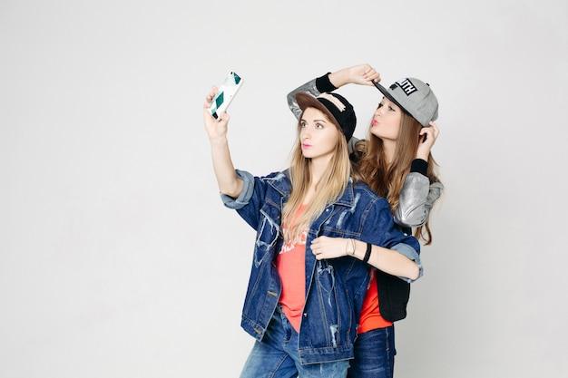 Twee swag zusters nemen zelfportret op telefoon. Premium Foto