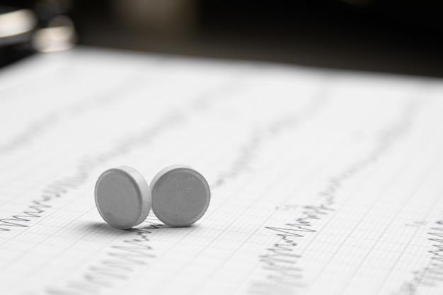 Twee tabletten op een elektrocardiogramvel Premium Foto