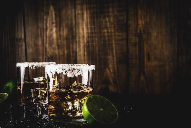 Twee tequila shot glazen op donkere achtergrond, met ijsblokjes, zout en limoenen Premium Foto