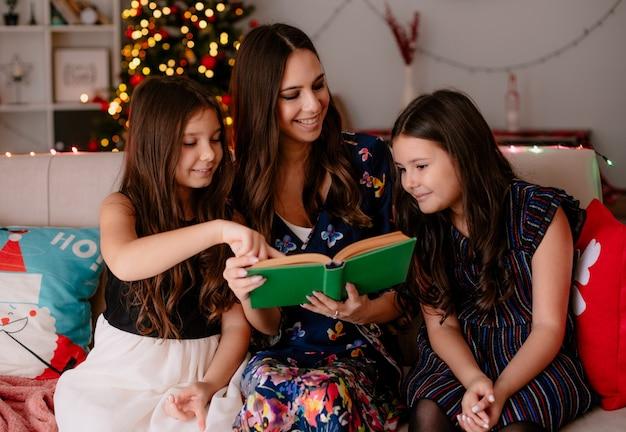 Twee tevreden zussen en jonge lachende moeder thuis in de kersttijd zittend op de bank in de woonkamer moeder leesboek aan dochters kijken naar oudere dochter jongere één wijzend naar boek Gratis Foto