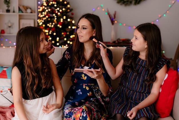 Twee tevreden zussen en jonge tevreden moeder thuis in de kersttijd zittend op de bank in de woonkamer make-up op elkaar te zetten terwijl ze naar elkaar kijken Gratis Foto