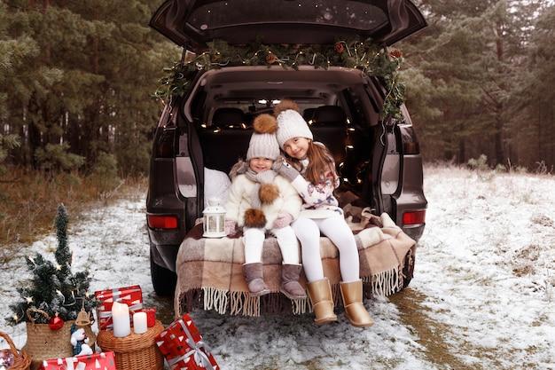 Twee tienermeisjes knuffelen in de kofferbak van een auto versierd met kerstversieringen Premium Foto