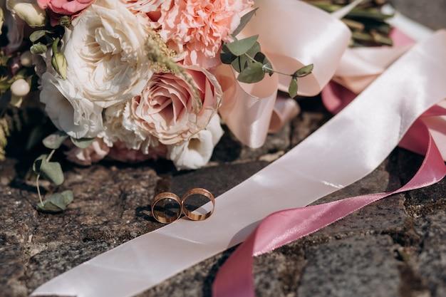 Twee trouwringen liggen op een band van een bruidsboeket Gratis Foto