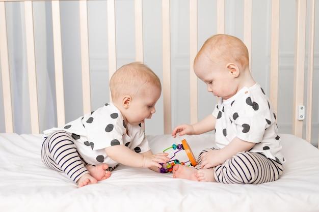 Twee tweelingbaby's van 8 maanden oud spelen in de wieg, vroege ontwikkeling van kinderen tot een jaar Premium Foto