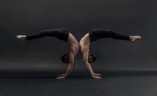 Twee tweelingbroers in zwarte jeans met een naakte torso voeren acrobatische elementen, zwarte achtergrond uit Premium Foto