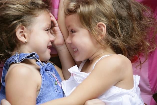 Twee tweelingzussen in een knuffel, sluiten omhoog Premium Foto