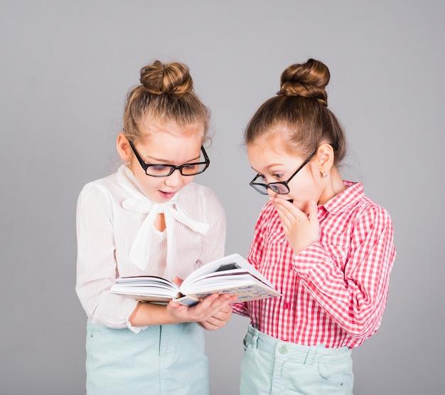 Twee verbaasde meisjes in glazen die boek lezen Gratis Foto