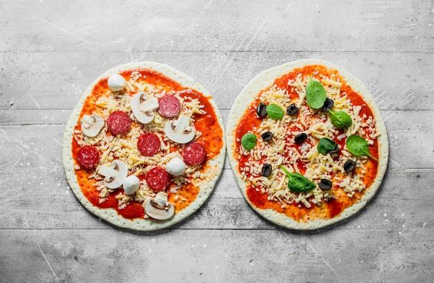 Twee verschillende rauwe pizza's op witte houten tafel Premium Foto