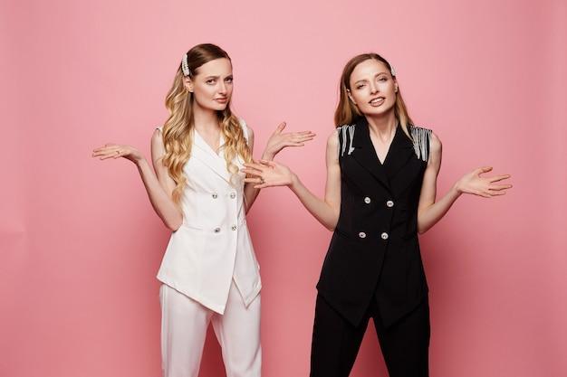 Twee verwarde vrouwelijke tweelingen in witte en zwarte trendy pakken Premium Foto
